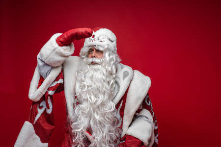 Festive Santa Claus look into the distance with hand on forehead on red background, copy space for holiday advertising