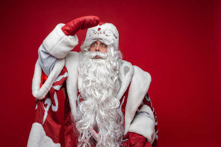 Senior Santa Claus looking away with hand at head. Stok Fotoğraf