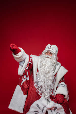 Senior Santa Claus with gray beard pointing by hand away on red background with copy space Stok Fotoğraf - 167152973