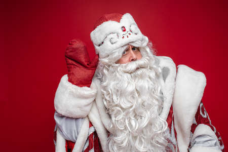 Santa with hand by ear listening carefully. Stok Fotoğraf