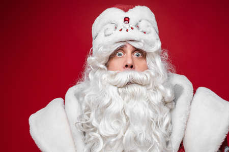 Surprised shocked Santa Claus, wondering senior male with gray beard, close up studio portrait on red background Stok Fotoğraf