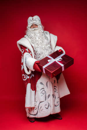 Full length Santa Claus with xmas gift on red studio background Stok Fotoğraf