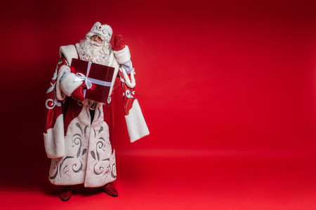 Santa Claus with xmas gift puts his hand to head, tryes to listen on red background with copy space for festive design