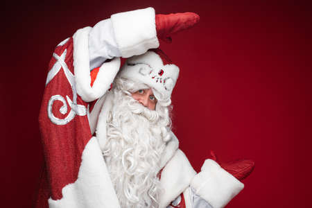 Happy Santa Claus shows size or dimension of discount by hands in mittens on red studio background with copy space