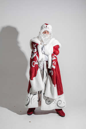picture of an old caucasian father frost in long warm coat, red mittens and a hat looks to the camera Stok Fotoğraf