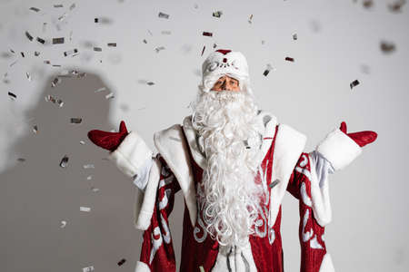 Santa claus under festive xmas confetti showing welcome gesture, studio holiday portrait for congratulations