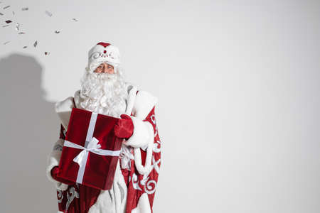 Santa Claus with red xmas gift posing in studio, elderly male with christmas present, copy space for holiday advertising Stok Fotoğraf