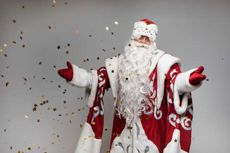 Santa Claus under golden stars confetti makes welcome gesture on gray background, card for xmas and new year design