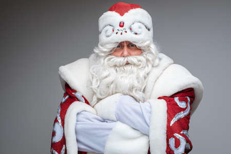 Serious Santa Claus crossed his arms over his chest and dissatisfied, studio portrait on gray background 스톡 콘텐츠
