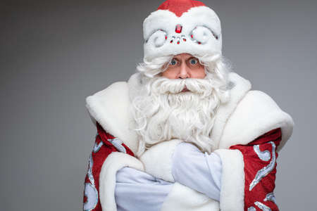 Dissatisfied Santa with arms folded looking at camera.
