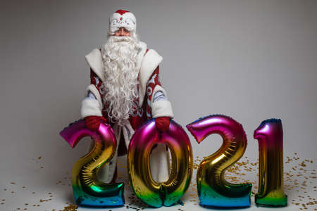 Santa Claus with colorful balloons in shape of 2021 on gray background with copy space, xmas and new year celebration