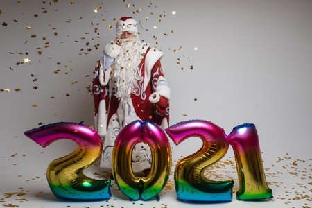 2021 new year celebration, santa claus with colorful balloons and confetti on gray studio background, copy space