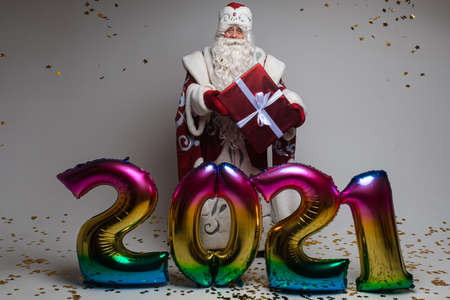 Colourful balloons in shape of 2021 and Santa with gift celebrating xmas and new year 스톡 콘텐츠
