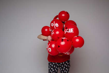 caucasian woman with a lot of red baloons with sales 스톡 콘텐츠