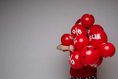 Young woman posing with many red balloons