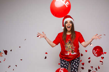 beautiful caucasian woman with a lot of red baloons with sales is surprised