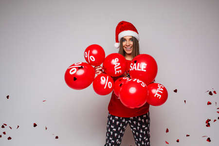 beautiful caucasian woman with a lot of red baloons with sales smiles 스톡 콘텐츠