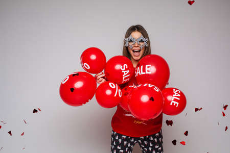 Smiling beautiful lady enjoying with red balloons in studio 스톡 콘텐츠
