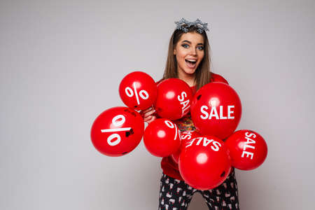 Pretty woman with Sale red air balloons holding bunch of red air balloons with sale and discount stickers. 스톡 콘텐츠
