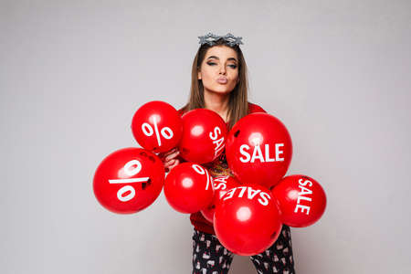 Attractive woman in pajamas with red balloons with inscription sale