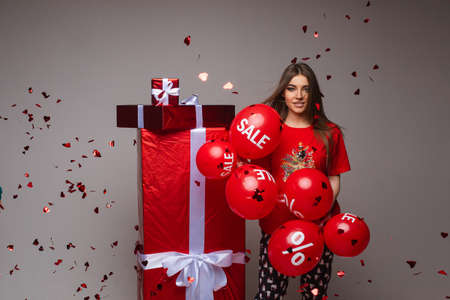 Pretty girl with balloons and giant presents. 스톡 콘텐츠
