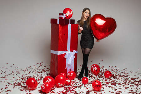 Cheerful brunette girl in dress pointing at presents.