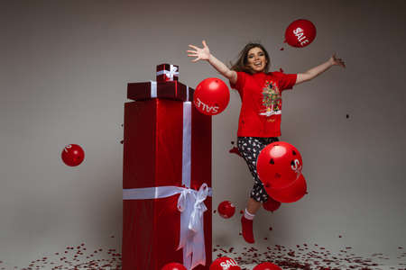 Woman in pajamas jumping with flying balloons and gifts.