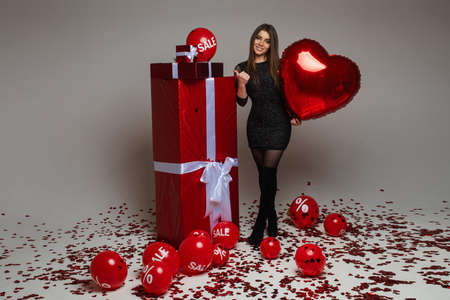 handsome caucasian woman poses for the camera near red boxes with presents and a lot of red baloons with sales and percents on them