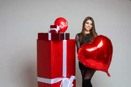 Smiling girl with heart shaped air balloon with wrapped presents. 스톡 콘텐츠