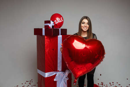 Smiling beautiful lady posing near red gift boxes in studio