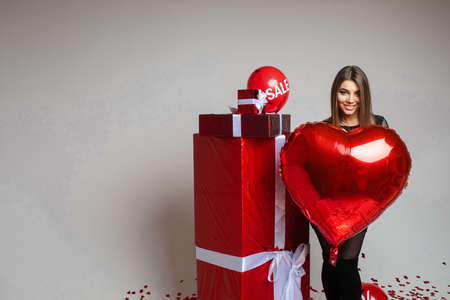 handsome caucasian woman poses for the camera near red boxes with presents and a big heart baloon in her hand 스톡 콘텐츠