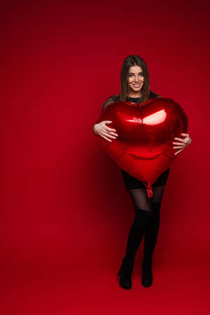 Heart shaped balloon in girls arms. Saint Valentine concept. 스톡 콘텐츠