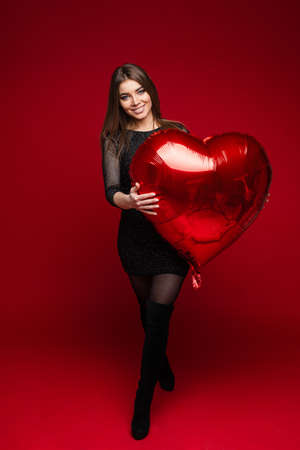 cheerful woman with straight dark hair holds a big red air baloon and smiles