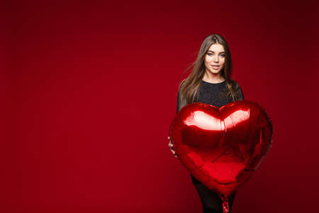 Pretty young elegant woman posing and holding red balloon in studio
