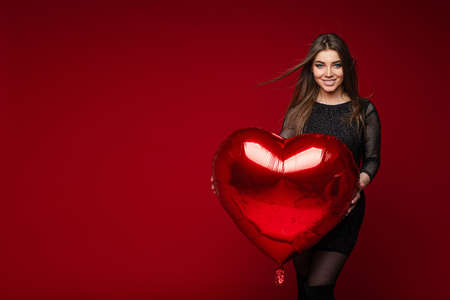 beautiful woman with straight dark hair holds a big red air baloon poses for the camera