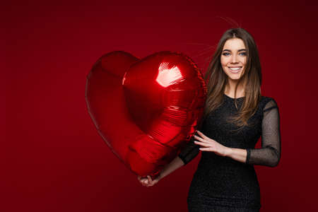 Smiling beautiful brunette woman in black dress with red balloon