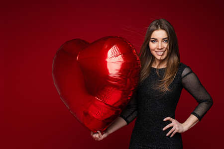 Smiling pretty woman with heart inflatable balloon.