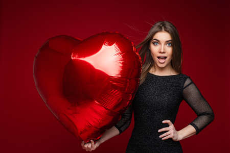 beautiful woman with straight dark hair holds a big red air baloon is surprised