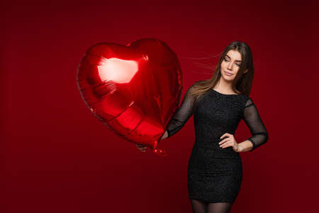 beautiful woman with straight dark hair and pretty smile holds a big red air baloon