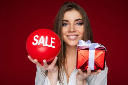 portrait of cheerful caucasian woman with red baloon with sale on it on the one hand and red box with a gift on the other