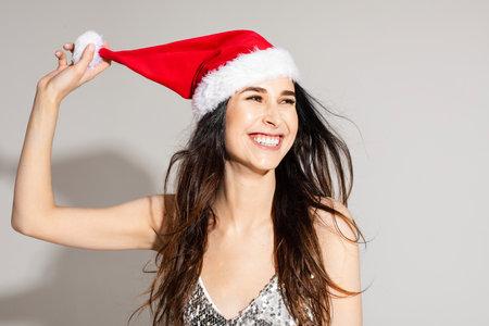 Happy beautiful young woman wearing Santa hat