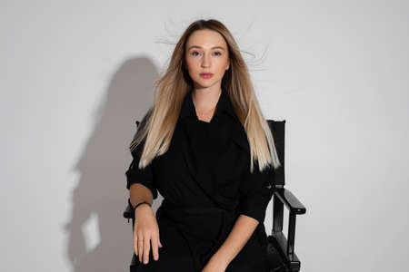 portrait of young caucasian woman in black dress sits on a chair isolated on white background