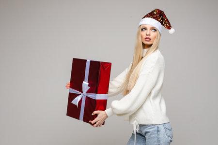 Beautiful woman in Santa hat posing with gift box