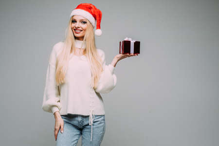 Pretty blonde lady posing with small gift box