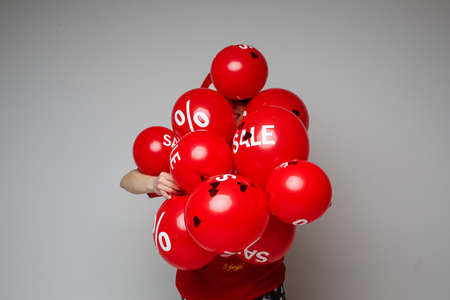 Holiday sale and discount, human hiding behind red balloons on gray background with blank space for advertising