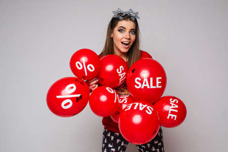 Joyful surprised positive young female with red balloons on gray background with copy space, sale and discount concept 스톡 콘텐츠