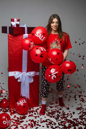Holiday sale, pretty young girl in pyjamas with red balloons and gifts on gray studio background with copy space for ad