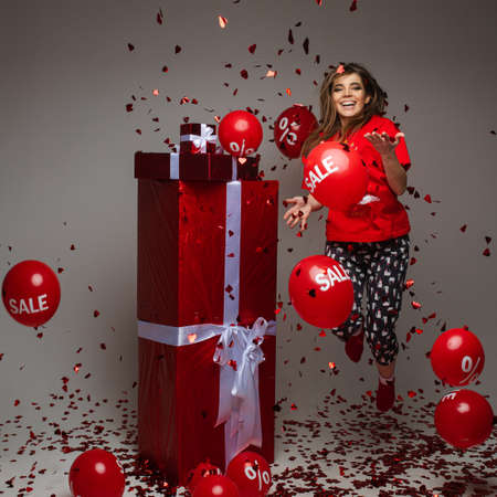 Celebrating young girl jumping under confetti with red gifts and balloons, holiday sale and discount concept