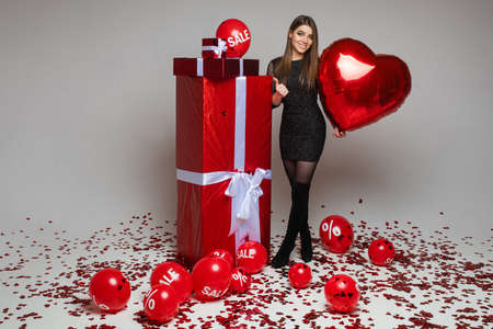 Slim pretty young girl in dress with red balloons, gifts and confetti on gray background, Valentine day sale concept