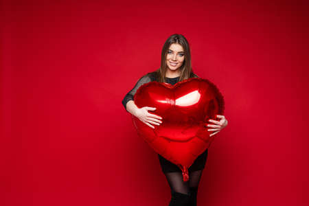 Valentine day holiday, young girl hugs heart shaped balloon with blank space for advertising on red background